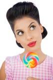 Zastanawiać się czarni włosy modela trzyma barwionego lizaka Zdjęcia Stock