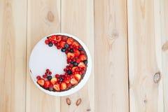 Zasycha z białą serową śmietanką, dekorującą z ganache i czerwieni jagodami na białym stojaku Tortów stojaki na drewnianym stole  obraz royalty free