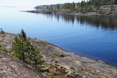 Zatoka jezioro skalisty brzeg zatoka i brzeg przerastający z rzadki lasowy Oddalonym przylądek, zakrywający z zwartym lasem zdjęcia royalty free