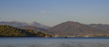 Zatoka w Fethiye, Turcja, w przedpolu woda zakrywa z czochrami, w tle szczyty góry Obrazy Royalty Free