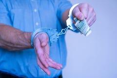 Zatrzymująca przestępca chce płacić daleko milicyjnego przedstawiciela Kajdanki na nadgarstkach zatrzymujący mężczyzna obraz royalty free