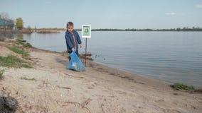 Zatrzymuje zanieczyszczenie, ślicznych chłopiec ciągnień ciężka grat na wskazywać znaka na rzeki plaży po czyścić w górę plastiko zbiory