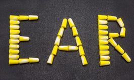 Zatyczka do uszu, dla ochrony przeciw hałasowi w żółtym i białym, W formie wpisowego ucho, odizolowywającego na czerni tła wi zdjęcie royalty free