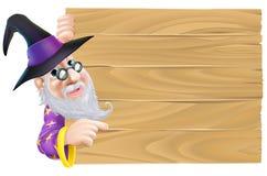 Zauberer, der auf hölzernes Zeichen zeigt Lizenzfreies Stockfoto