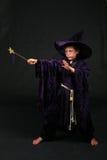 Zaubererjunge mit dem magischen Stab, der einen Bann wirft Lizenzfreie Stockbilder