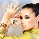 Zauberfrau mit schönen goldenen Nägeln und Smaragdring Stockfotos