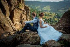 Zauberjungvermähltenpaar sitzt auf dem Rücken an Rückenfelsen und genießt die Landschaftsansicht während des sonnigen Tages stockfoto