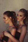 Zaubermake-up zwei Frauen mit der langen Frisur, die auf Straße sitzt, ummauert Hintergrund in der Dunkelheit Modefarbporträt, üb Stockfotografie