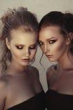 Zaubermake-up zwei Frauen mit der langen Frisur, die auf Straße sitzt, ummauert Hintergrund in der Dunkelheit Modefarbporträt, üb Stockfoto