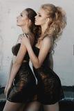 Zaubermake-up zwei Frauen mit der langen Frisur, die auf Straße sitzt, ummauert Hintergrund in der Dunkelheit Modefarbporträt, üb Lizenzfreie Stockfotografie