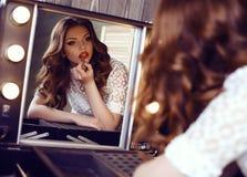 Zaubermädchen mit dem dunklen gelockten Haar, das Make-up, Farben ihre Lippen, Spiegel betrachtend macht Stockbild