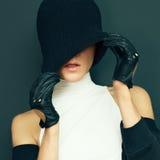 Zaubermodell auf schwarzem Hintergrund in den modischen Handschuhen und im Hutherbst Lizenzfreies Stockfoto