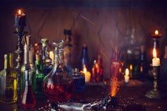 Zaubertrank, alte Bücher und Kerzen Lizenzfreies Stockfoto