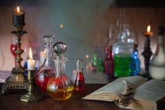 Zaubertrank, alte Bücher und Kerzen Lizenzfreie Stockfotografie