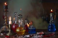 Zaubertrank, alte Bücher und Kerzen Stockbilder