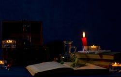 Zaubertrank, alte Bücher und Kerzen auf dunklem Hintergrund Stockbild