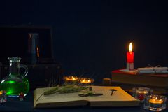 Zaubertrank, alte Bücher und Kerzen auf dunklem Hintergrund Stockfotos