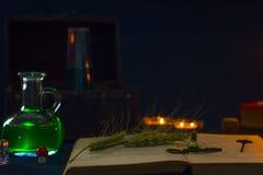 Zaubertrank, alte Bücher und Kerzen auf dunklem Hintergrund Lizenzfreie Stockbilder