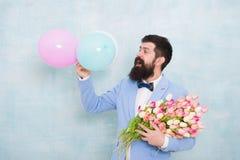 Zaufanie i charyzma Obsługuje brodatego dżentelmenu kostiumu łęku krawata chwyta lotniczych balony i bukiet Dżentelmen robi roman zdjęcia stock