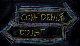 Zaufanie lub wątpliwość pisać z kolor kredy pojęciem na blackboard zdjęcie stock