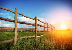 Zaun auf dem grünen Gebiet unter blauem Wolkenhimmel Stockfotos