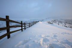 Zaun in den Bergen bedeckt im Schnee Stockbilder