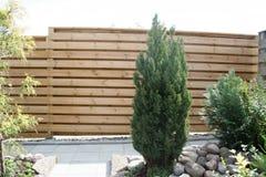 Zaun des Holzes, das den Garten umgibt und vor Wind und Ansicht sich schützt Stockfotografie