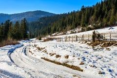 Zaun durch die Straße zum schneebedeckten Wald in den Bergen Stockfoto