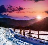 Zaun durch die Straße zum schneebedeckten Wald in den Bergen Lizenzfreies Stockfoto