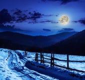 Zaun durch die Straße zum schneebedeckten Wald in den Bergen Stockbild