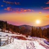 Zaun durch die Straße zum schneebedeckten Wald in den Bergen Lizenzfreies Stockbild