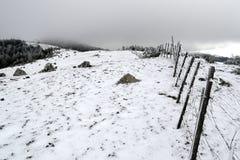 Zaun entlang einem geschneiten breiten Gebirgsrücken unter dunklen Wolken Stockfotos
