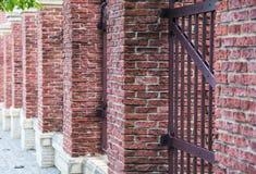 Zaun hergestellt vom roten Backstein Stockfotografie