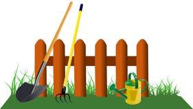 Zaun im Gras mit Gartenwerkzeugen Stockbilder