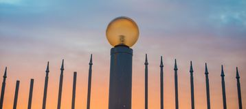 Zaun mit scharfen Spitzen und Straßenlaterne am Abend Straßenlaterne auf dem Hintergrund eines schönen Sonnenunterganghimmels lizenzfreies stockbild