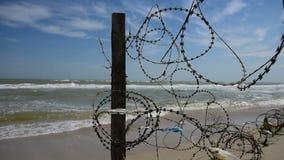 Zaun mit Stacheldraht auf Hintergrund von Meer stock video footage