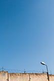 Zaun mit Stacheldraht und Laterne gegen den blauen Himmel Stockfotos