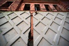 Zaun mit unfertigem Haus des Stacheldrahts und des Ziegelsteines Lizenzfreie Stockbilder