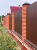 Zaun mit Ziegelsteinsäulen Stockfotografie
