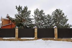Zaun nahe dem Haus mit Kiefern, im Winter Stockfoto