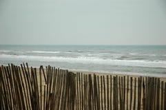 Zaun am Strand mit Ozean Lizenzfreie Stockfotos
