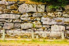 Zaun und schmaler Weg entlang nasser Steinwand Stockfoto