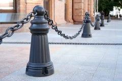 Zaun von Metallpfosten und -ketten auf der Straße Stockfotografie
