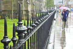 Zaungeländer, Fußgänger mit dem Regenschirmgehen stockfoto