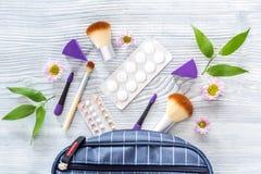 Zawartość wonam ` s piękna torba Kosmetyki, antykoncepcyjny i pigułki na drewnianego stołowego tła odgórnym widoku, Zdjęcia Stock