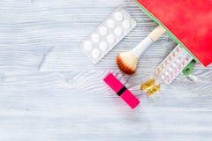 Zawartość wonam ` s piękna torba Kosmetyki, antykoncepcyjny i pigułki na drewnianym stołowym tło odgórnego widoku copyspace, Zdjęcia Royalty Free