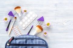 Zawartość wonam ` s piękna torba Kosmetyki, antykoncepcyjny i pigułki na drewnianym stołowym tło odgórnego widoku copyspace, Fotografia Royalty Free