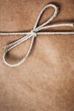 Zawiązuje wiązanego w łęku nad brown pakunku papierem, Zdjęcie Royalty Free