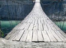 Zawieszenie most nad halnym strumieniem obrazy royalty free