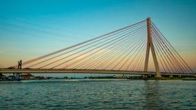 Zawieszenie most nad rzeką przy zmierzchem fotografia stock